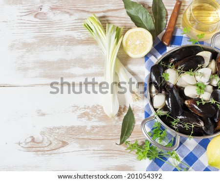 Mussels with fresh parsley and thyme onion on white wooden table - stock photo