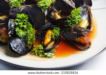 Mussels with tomato sauce served in plate - stock photo