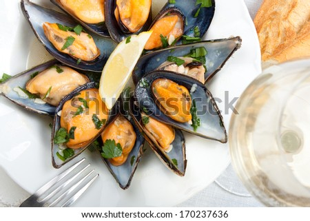 Mussels with white wine and parsley sauce with a glass of white wine and bread