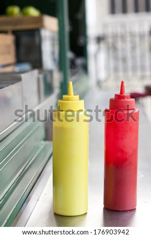 Mustard and Ketchup bottles on a burger stand - stock photo