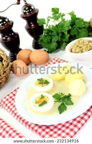 Mustard eggs with potatoes on a light background - stock photo