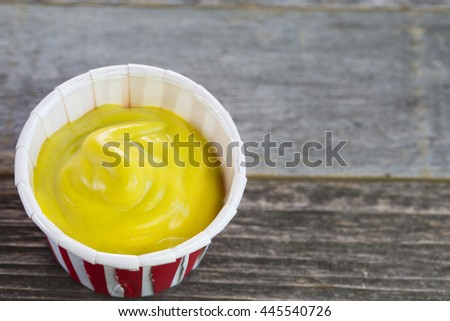 Mustard in a paper serving cup close up. - stock photo