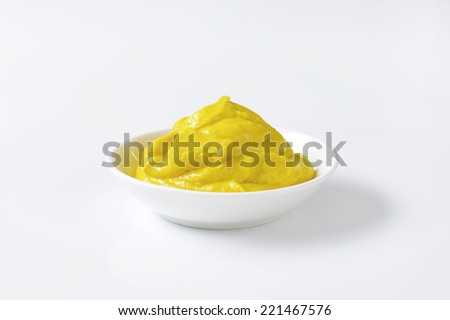 Mustard in a porcelain bowl - stock photo