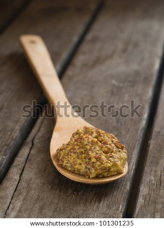 Mustard sauce with seeds  in wooden spoon, selective focus