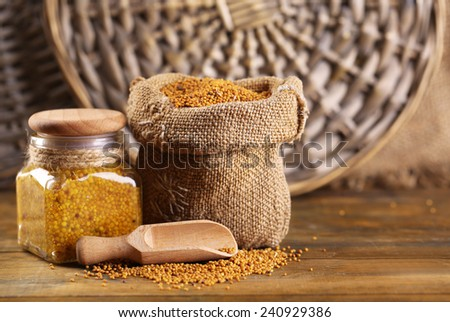 Mustard seeds in bag and Dijon mustard in glass jar on wooden background - stock photo