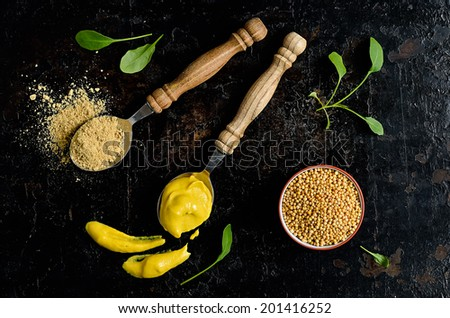 Mustard seeds, powder and ready mustard spice on a dark background - stock photo