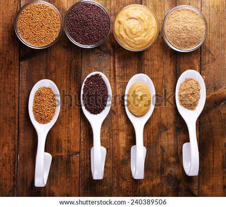 Mustard seeds, powder and sauce in spoons  and bowls on wooden background - stock photo