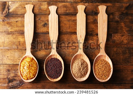 Mustard seeds, powder and sauce in wooden spoons on wooden background - stock photo