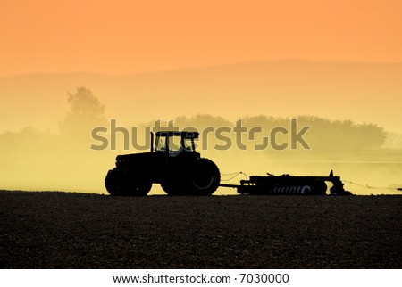 Muted Backlit Silhouette of Tractor Raking Soil - stock photo