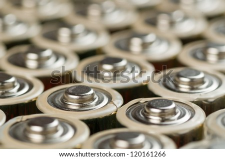 Mutiple Gold Batteries in Rows with Silver Tops Closeup - stock photo