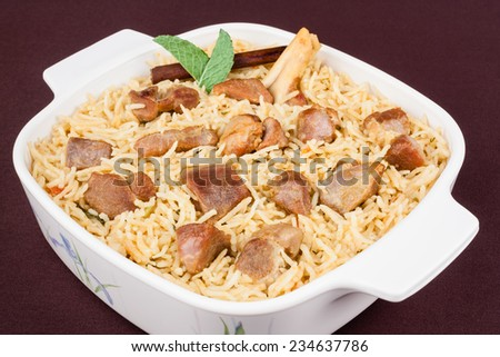 Mutton Biryani - Closeup view from the top of delicious mutton (lamb) biryani garnished with with mint and cinnamon. - stock photo