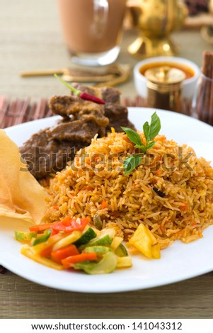 Mutton Biryani rice with traditional items on background - stock photo