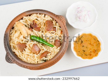 Mutton Biryani with Salad - Overhead view from the top of delicious mutton (lamb) biryani with garnish. Served in an earthenware bowl with salad (raita) and gravy. - stock photo