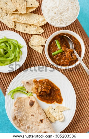 Mutton rogan josh meal - Tasting Indian mutton rogan josh meal with rice and chapati. This spicy hot Kashmiri dish uses red chilli (cayenne pepper) as its main ingredient. Natural light used. - stock photo