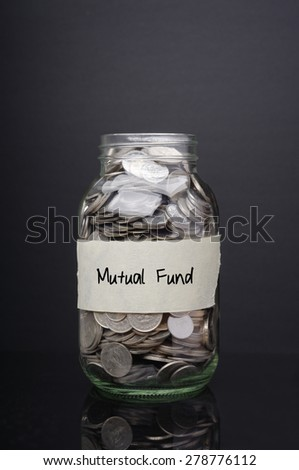 Mutual fund label on glass jar with coins - stock photo