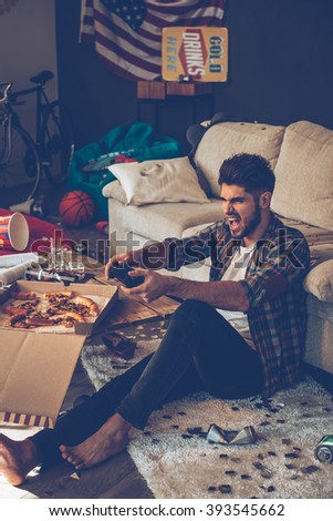 My best lap! Excited young man holding joystick and keeping mouth open while sitting on the floor in messy room after party - stock photo