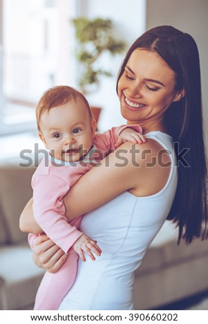 My best little friend! Beautiful young woman holding baby girl in her arms and looking at her with love while standing at home - stock photo