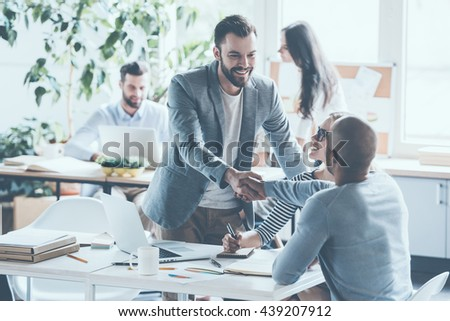 My congratulations! Two cheerful businessmen shaking hands while being in office together with their colleagues  - stock photo