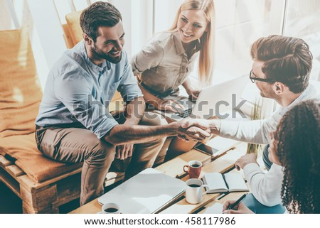 My congratulations! Two cheerful young men sitting at the wooden desk in office and shaking hands while two beautiful women looking at them and smiling