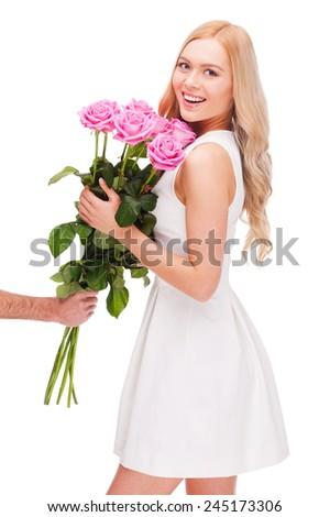 My favorite flowers! Male hand stretching out bouquet of pink flowers while beautiful young smiling woman in dress taking it  - stock photo