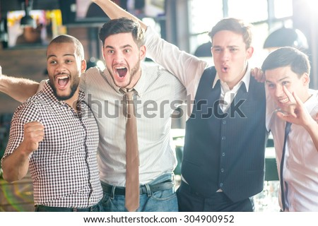 My favorite program on TV. Four friends standing arm in arm at the bar and look at the TV and shout loudly and laughing. Friends having fun together - stock photo