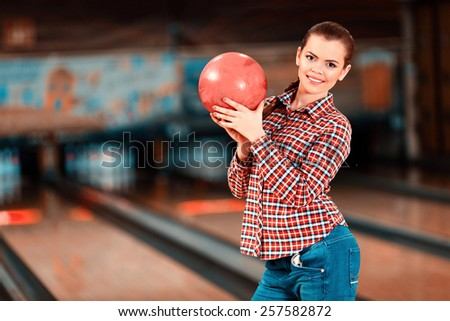 My lucky ball. Beautiful young women holding a bowling ball while standing against bowling alleys - stock photo