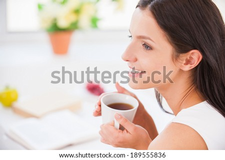 My morning coffee. Side view young smiling woman sitting in bed and holding a cup while covered with blanket - stock photo