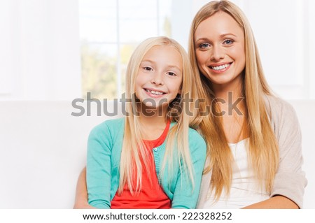 My mother is my best friend. Happy mother and daughter bonding to each other and smiling while sitting on the couch together  - stock photo