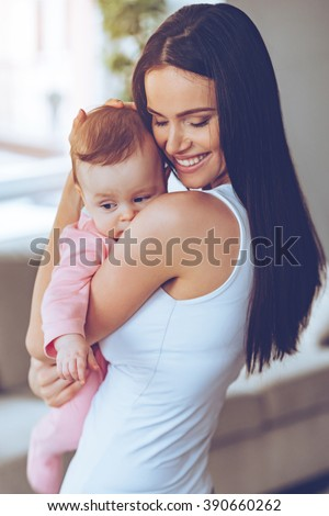 My sweet little girl! Beautiful young woman holding baby girl in her arms and bonding with her while standing at home - stock photo