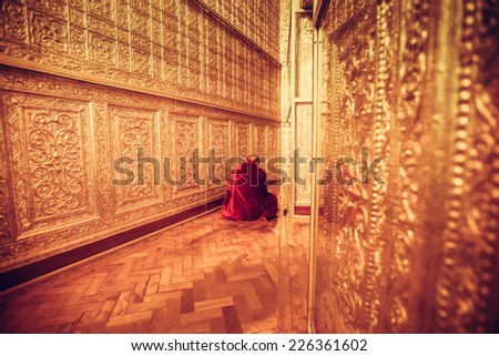 MYANMAR - FEBRUARY 9: Unidentified Monk in Red suit make meditation in big golden room at Botataung pagoda on February 09, 2014 in Yangon, Myanmar - stock photo
