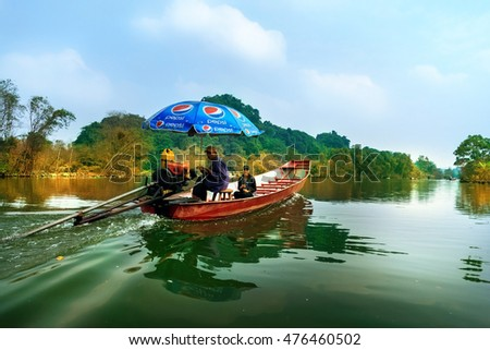 MYDUC, VIETNAM - October 19, 2014: Man controls motor boat in the flooded forest in MYDUC, VIETNAM. MYDUC is a district about 60 km from Hanoi.