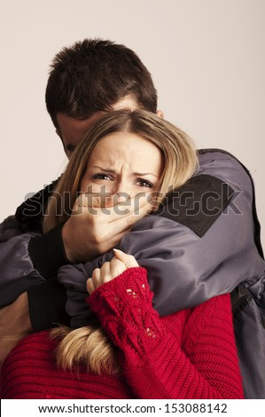 Mysteriious man kidnapping young woman - stock photo