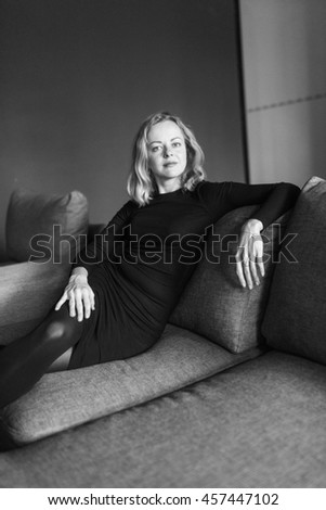 Mysterious beautiful lady relaxing on the couch