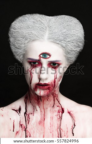 Mysterious beauty portrait of snow queen covered with blood. Bright luxury makeup. Gore dripping from the mouth