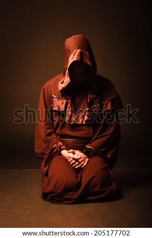 mysterious Catholic monk in twilight. studio shot - stock photo