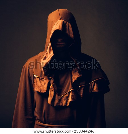mysterious Catholic monk on dark background. studio shot - stock photo