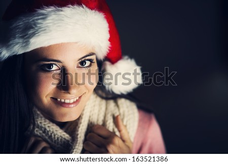 Mysterious christmas woman in santa hat at dark background