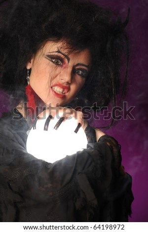 Mysterious fortune telling woman with glowing crystal ball looking at the camera