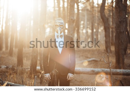 Mysterious handsome businessman in a traditional venetian mask, wearing a suit in the Autumn forest  - stock photo