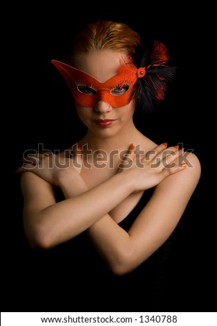 mysterious lady in red mask holding her arms in w shape - stock photo