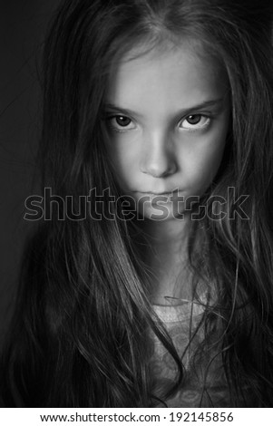 Mysterious little girl with long hair, black and white photography. - stock photo