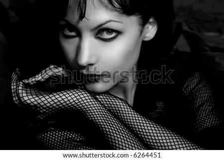 Mysterious low-key portrait of beautiful glamorous woman in hat. Soft-focused. Focus is on eye - stock photo