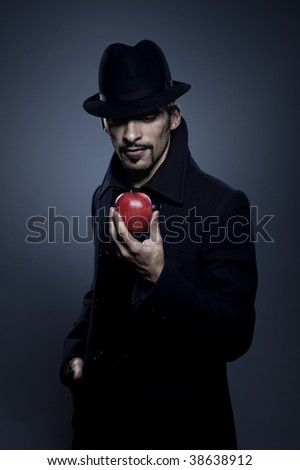 Mysterious man holding an apple - stock photo