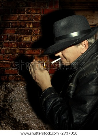 Mysterious man, mafia guy or secret police, waiting in the dark and lighting a cigarette - stock photo