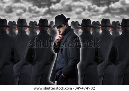 Mysterious man making a silence gesture while standing out from the crowd - stock photo