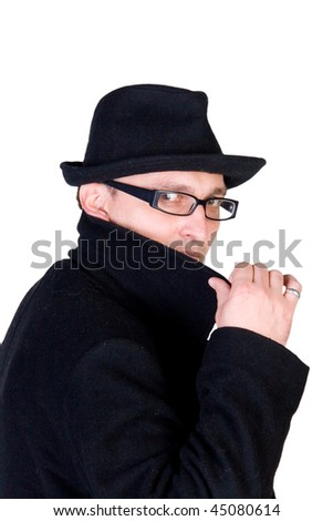 Mysterious man wearing a black hat and a black coat with a raised collar - stock photo