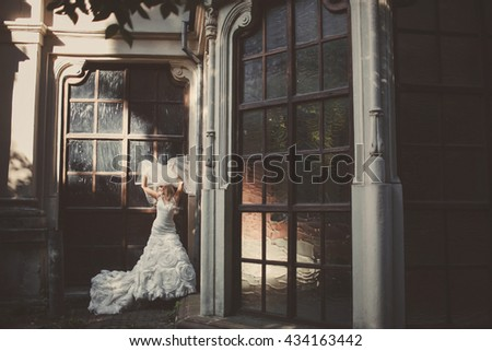 Mysterious picture of beautiful bride posing behind an old porch - stock photo