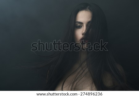 mysterious portrait of a girl in the dark, in the fog - stock photo