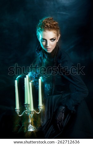 Mysterious portrait of beautiful females,  girl holds a candle stand extinguished candles, soft effect - stock photo