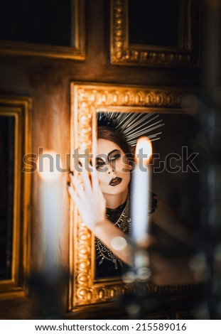 Mysterious portrait of beautiful goth girl looking into the mirror - stock photo